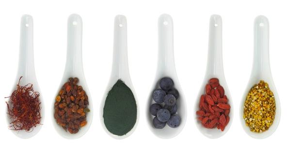 Superfoods in porcelain spoons. Pollen, goji berries, blueberries, spirulina, Hippophae and saffron